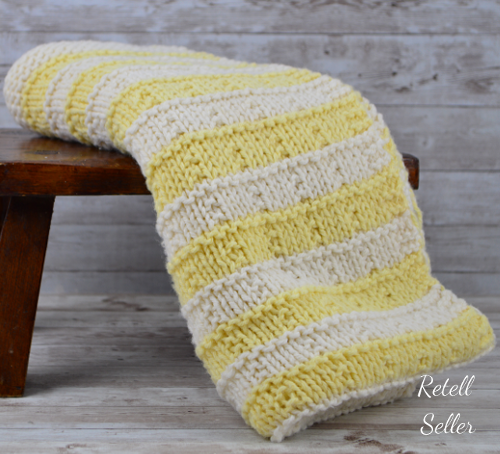 A muted, soft colored, yellow and white afghan.