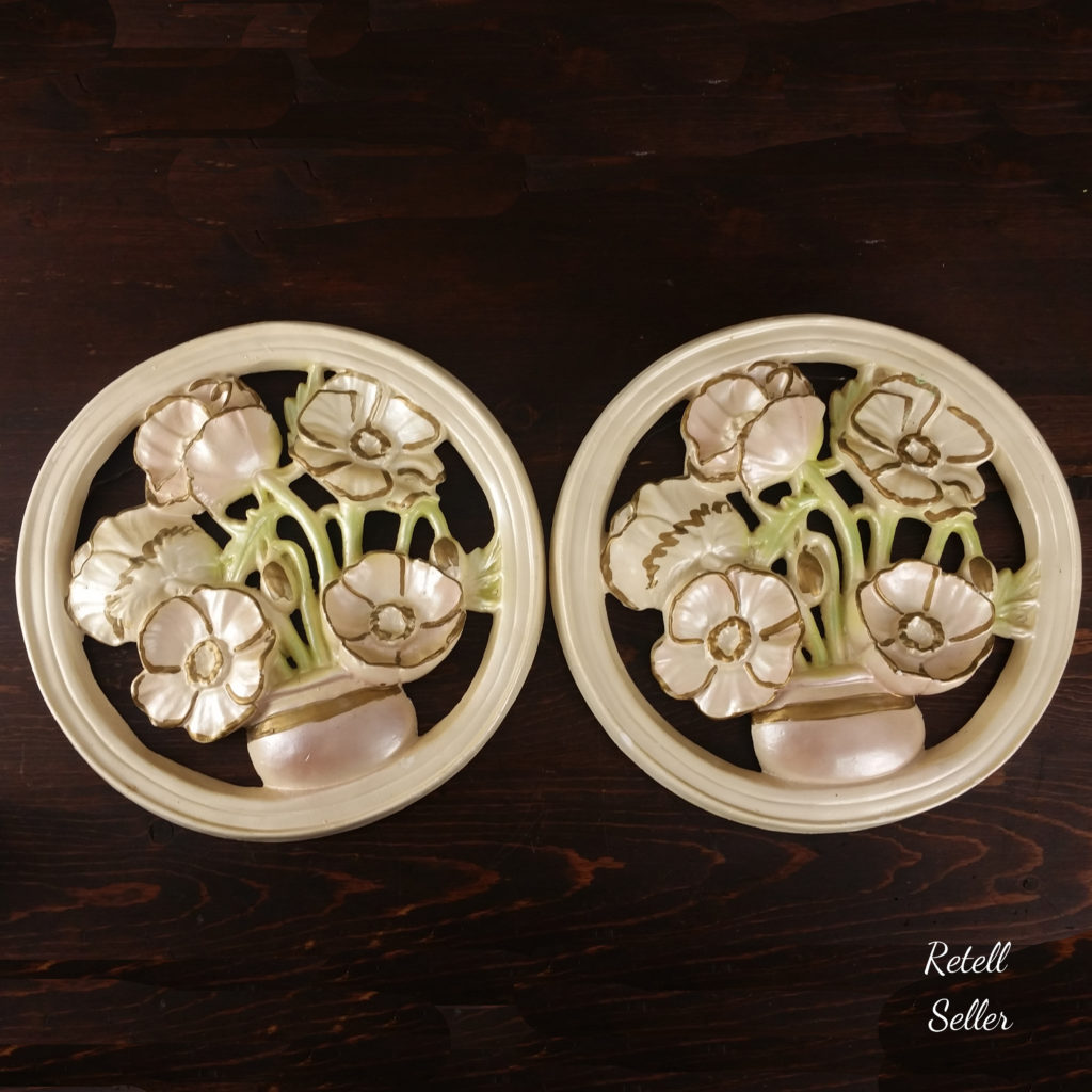 2 round vintage plasterware wall hangings of potted flowers. Beautiful pastel colors with a shimmery vibe.