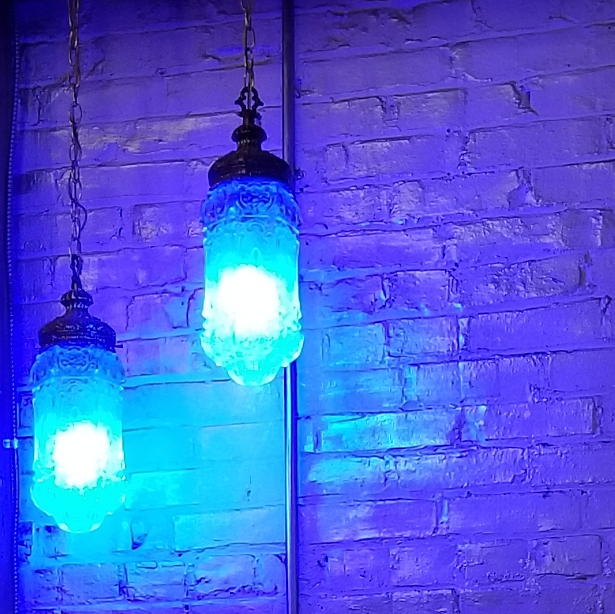 Electric blue colored bulbs in a double swag lamp.