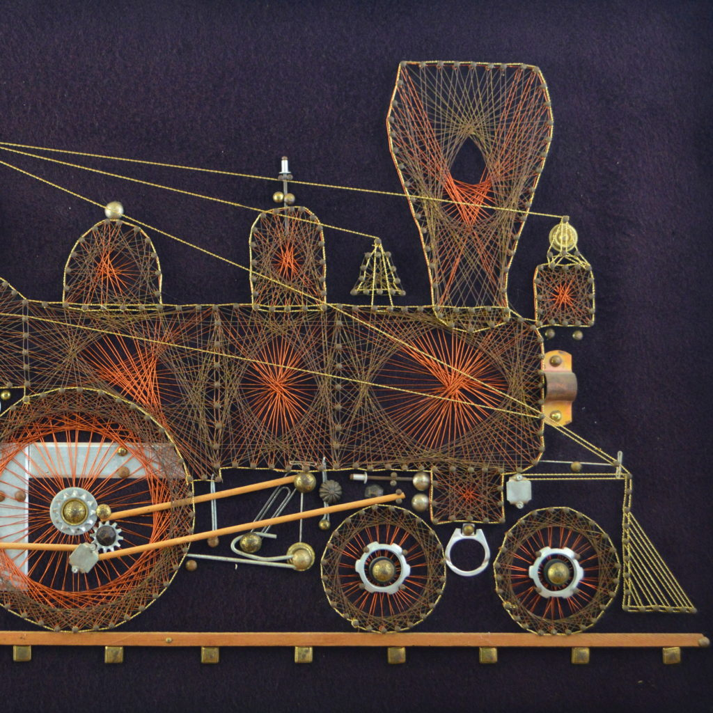 Vintage 1970s string art made of tacks, soda tabs, copper, and golden colored string to make a beautiful locomotive.